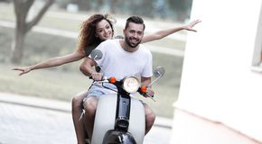 Young couple riding motor scooter in city stock photos