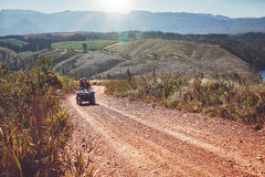 Young couple riding quad bike on country road Royalty Free Stock Image