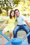 Young Couple Riding On Roundabout In Park Stock Photo