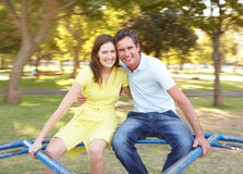 Young Couple Riding On Roundabout In Park Stock Image