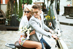 Young couple riding a scooter on their date Royalty Free Stock Image