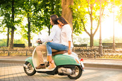 Young couple riding a scooter Stock Photography