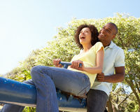 Young Couple Riding On SeeSaw In Park royalty free stock images