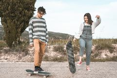 Young couple riding a skateboard on a road. Concept of millenials Skateboarders stock photos