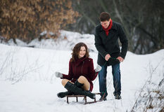 Young couple riding on a sled Stock Photography