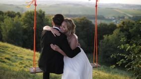 Young couple riding on a swing. Enjoying the Togetherness. Amazing landscape Royalty Free Stock Image