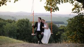 Young couple riding on a swing. Enjoying the Togetherness. Amazing landscape Stock Photo