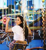 Young couple riding the swings at an amusement park.  Stock Photos