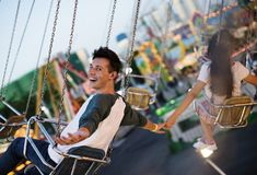 Young couple riding the swings at an amusement park Royalty Free Stock Images