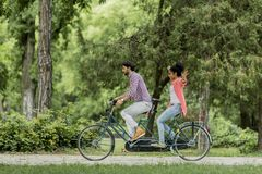 Young couple riding on the tandem bicycle Royalty Free Stock Image