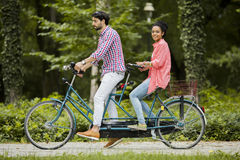Young couple riding on the tandem bicycle Royalty Free Stock Images