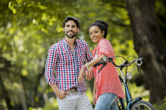Young couple riding on the tandem bicycle Stock Image