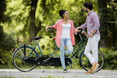 Young couple riding on the tandem bicycle Stock Photos