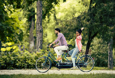 Young couple riding on the tandem bicycle Stock Images