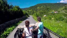 Young couple on the road in a jeep with an open top in the mountains. The guy and the girl are traveling on a pickup. Truck stock video