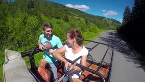 Young couple on the road in a jeep with an open top in the mountains. The guy and the girl are traveling on a pickup stock footage