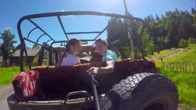 Young couple on the road in a jeep with an open top in the mountains. The guy and the girl are traveling on a pickup. Truck stock video footage