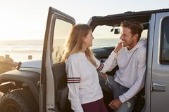 Young couple on road trip looking at each other by their car stock image