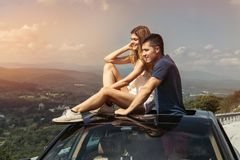 Young couple on road trip travel by car together and enjoy the nature view from the top.  royalty free stock images