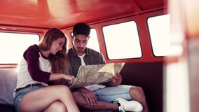A young couple on a roadtrip through countryside, looking at a map. A young couple on a roadtrip through countryside, sitting in retro minivan and looking at a stock video
