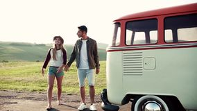 A young couple on a roadtrip through countryside, walking and talking. Slow motion stock video