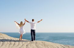 Young couple on a rock raised hands to the sky Royalty Free Stock Images