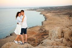 Young couple on the rock with the spectacular view on the background stock photography
