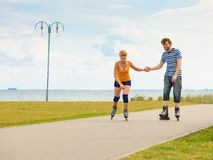 Young couple on roller skates riding outdoors Royalty Free Stock Photos