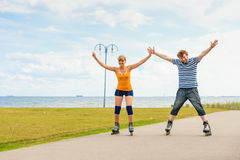 Young couple on roller skates riding outdoors Stock Photo