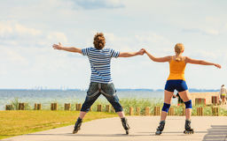 Young couple on roller skates riding outdoors Stock Photography