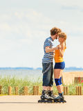 Young couple on roller skates riding outdoors Royalty Free Stock Images