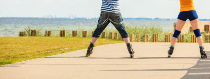 Young couple on roller skates riding outdoors Royalty Free Stock Photography