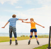 Young couple on roller skates riding outdoors Stock Photos