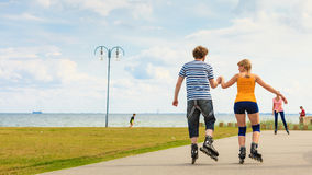 Young couple on roller skates riding outdoors Royalty Free Stock Image
