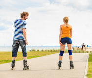 Young couple on roller skates riding outdoors Stock Image