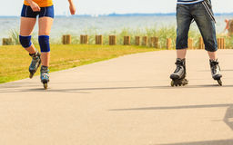 Young couple on roller skates riding outdoors Stock Photos