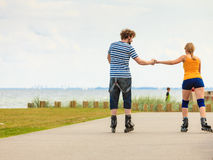 Young couple on roller skates riding outdoors Royalty Free Stock Photo