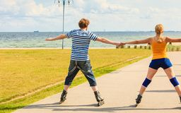Young couple on roller skates riding outdoors Stock Images