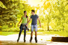 Young couple roller-skating in the park Stock Images