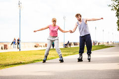 Young couple rollerblading in park holding hands. Royalty Free Stock Photography