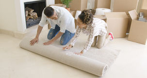 Young couple rolling up a rug as they move house Royalty Free Stock Images