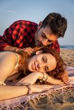 Young couple in romantic attitude on the sand of a Mediterranean beach at sunset. And the boy is whispering in the ear to the girl royalty free stock photography