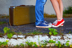 Young couple.Romantic meeting.Suitcase, jeans and sneakers. Abstract image of a loving couple.The photo is tinted in a retro style royalty free stock photography