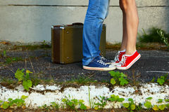 Young couple.Romantic meeting.Suitcase, jeans and sneakers. Stock Image