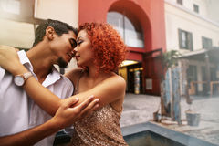 Young couple in a romantic mood out in the street. Close up of a young couple in a sensual pose about to kiss. Woman embracing men with eyes closed touching Royalty Free Stock Photos