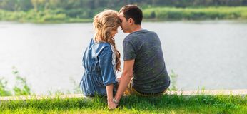 A young couple is romantic in the park on a lake. Man and woman sit in the summer sun in the green grass Stock Image