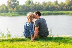 A young couple is romantic in the park on a lake. Man and woman sit in the summer sun in the green grass Royalty Free Stock Image