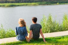 A young couple is romantic in the park on a lake. Man and woman sit in the summer sun in the green grass Stock Photos