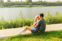 A young couple is romantic in the park on a lake. Man and woman sit in the summer sun in the green grass Stock Photography