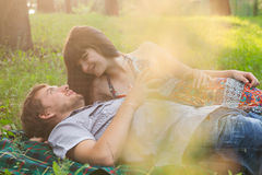 Young couple on a romantic picnic outdoors. Young couple on a romantic picnic in a park on a sunny day outdoors Royalty Free Stock Photos